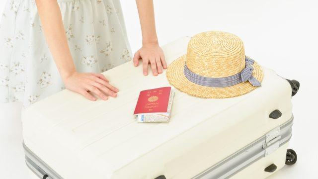 キャリーバッグに荷物を詰める女性の画像