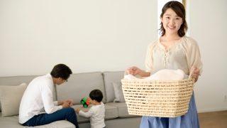 遊ぶ父と子と洗濯物のかごを持つ母