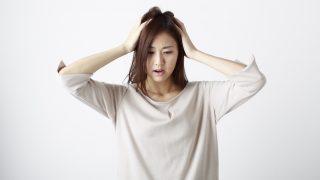 頭を抱えて困っている女性の画像